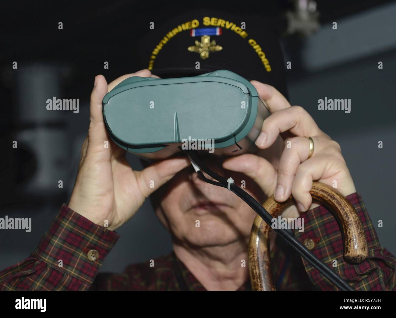 Retired U.S. Army 1st Sgt. Claude Quick, Legion of Valor member, looks through simulation binoculars at the Maritime Intermodal Training Department while on a tour at Joint Base Langley-Eustis, Va., April 21, 2017. Each year, members of the Legion of Valor gather for an annual convention to enhance their understanding of current military affairs and provide mentorship from personal accomplishments or failures. Stock Photo
