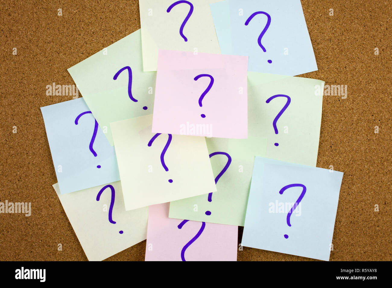 A yellow sticky note writing, caption, inscription Pile of colorful paper notes with question marks. Closeup. Stock Photo