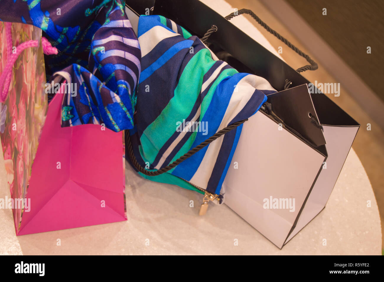Paper shopping bags with fashionable clothes bought in the store - Stock Image