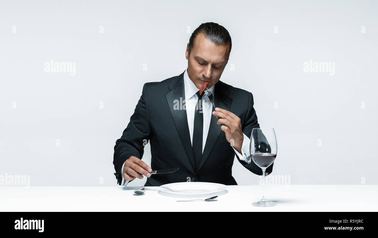Bloody Halloween theme: crazy man with a knife, fork and meat Stock Photo
