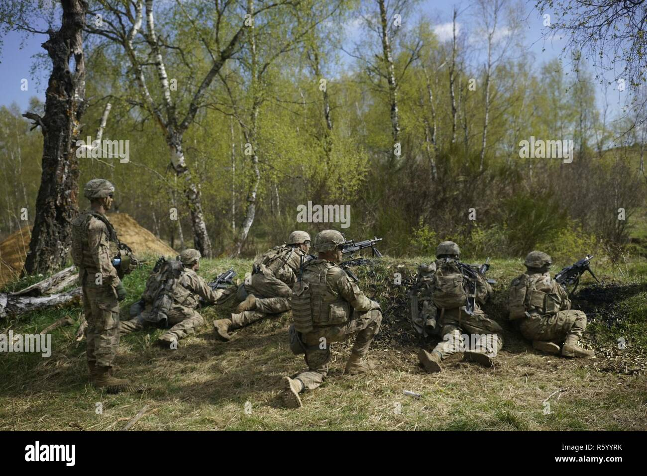 U.S. Soldiers of Comanche Troop, 4th Squadron, 10th Cavalry Regiment, 3rd Armored Brigade Combat Team, 4th Infantry Division provides suppressive fire with an M240 while conducting a live fire operation during Exercise Combined Resolve VIII at the Grafenwoehr Training Area, Germany April 24, 2017. Exercise Combined Resolve VIII is a multinational exercise designed to train the Army's Regionally Allocated Forces to the U.S. European Command. Combined Resolve VIII will include more than 3,400 participants from 10 nations. The goal of the exercise is to prepare forces in Europe to operate togethe - Stock Image