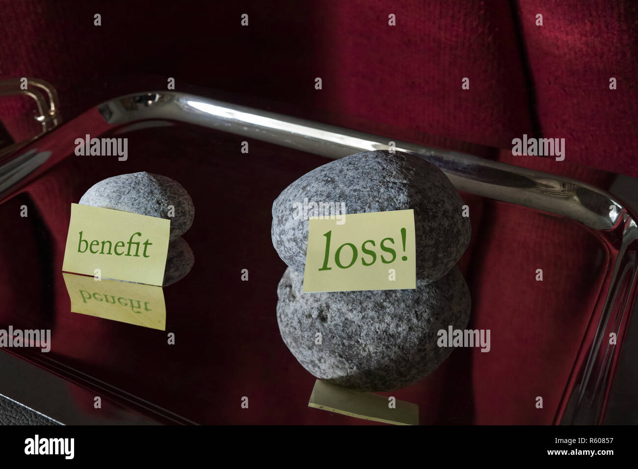 Two stones on a silver platter. A bigger one with a post-it in front, it says 'losses', a smaller one with a post-it in front where it says 'benefit'. - Stock Image