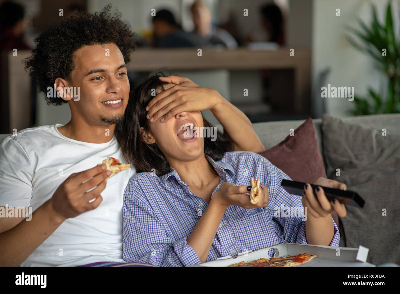Happy couple watching tv while eating pizza. Shallow depth of field, focus on the man - Stock Image