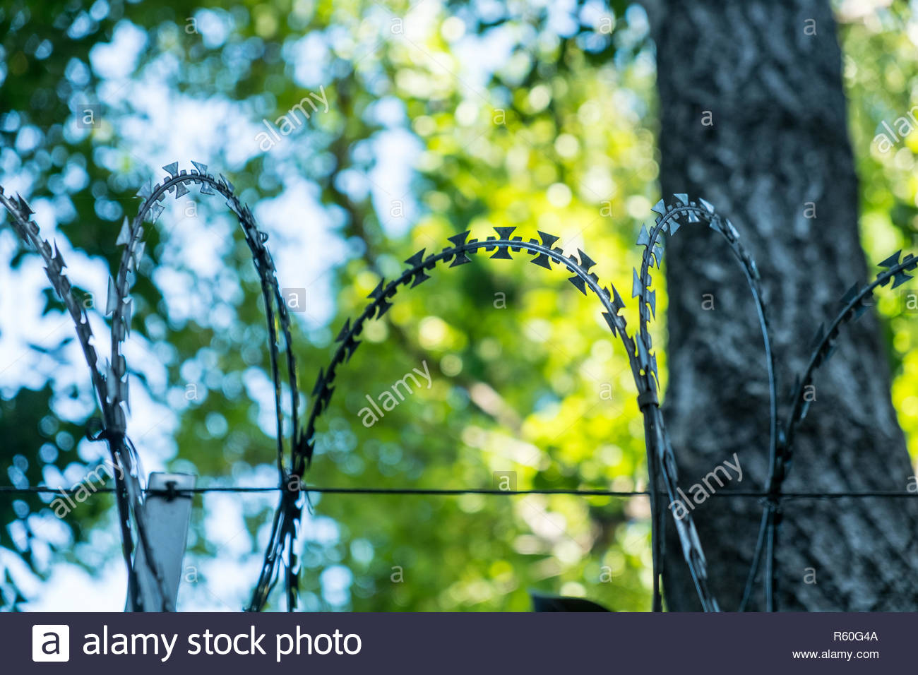 Portable barrier of sword blades. Barricades on the stone wall. Stock Photo