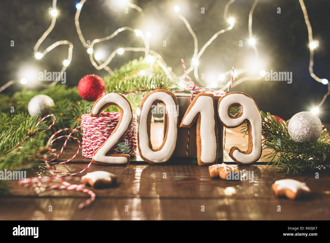 2019 greeting made of cookies and christmas lights. Christmas or New Year banner, decorations, greeting card - Stock Image