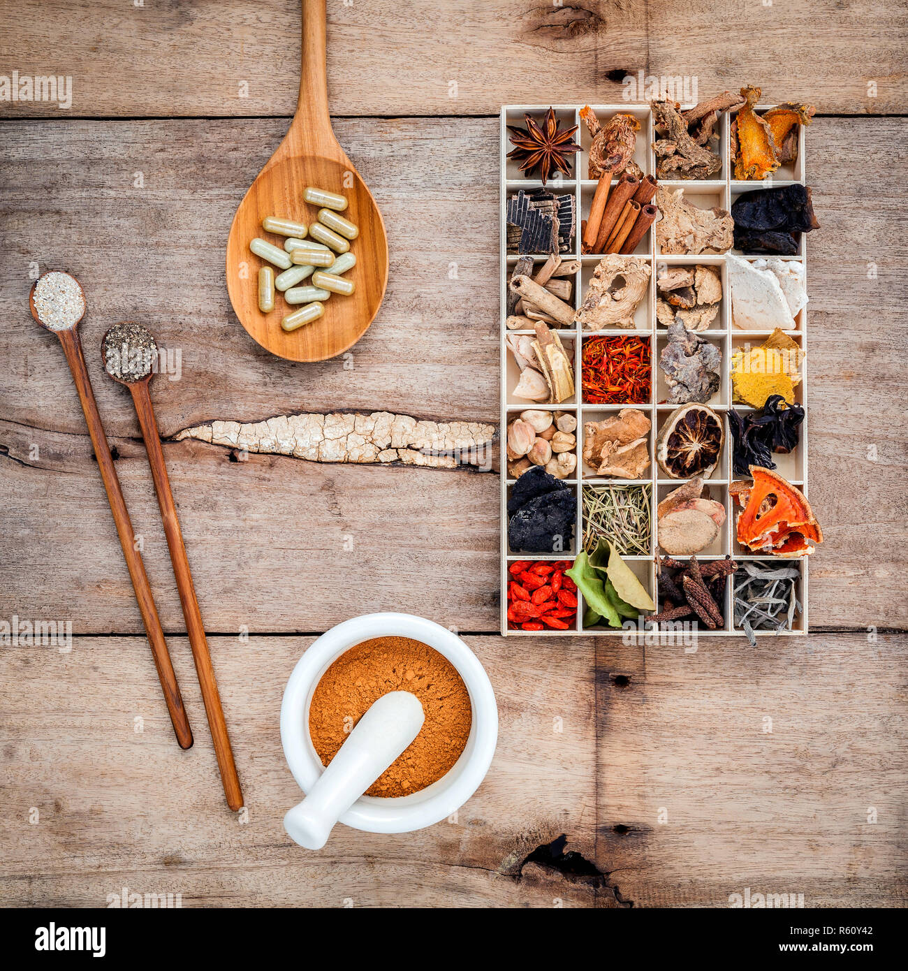 Alternative health care dried various Chinese herbs in wooden box and herbs capsule in wooden spoon with mortar on old wooden background. - Stock Image