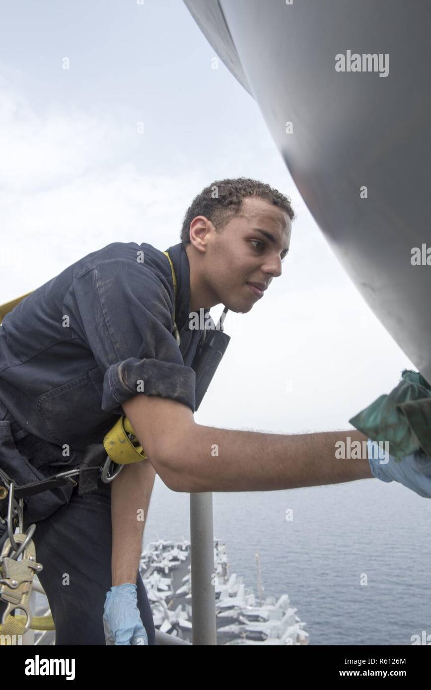 ARABIAN GULF (May 4, 2017) Electronics Technician 3rd Class Drew Ables wipes down an OE-570 satellite aboard the aircraft carrier USS George H.W. Bush (CVN 77) (GHWB). GHWB is deployed in the U.S. 5th Fleet area of operations in support of maritime security operations designed to reassure allies and partners, and preserve the freedom of navigation and the free flow of commerce in the region. - Stock Image