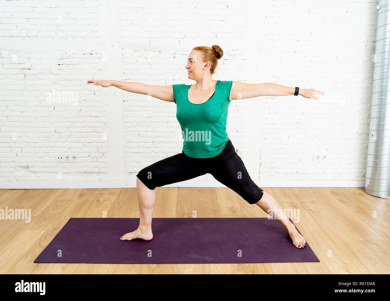 Portrait of young attractive Yoga teacher practicing standing in Warrior two exercise Virabhadrasana II pose in Fitness Working out Yoga benefits and  Stock Photo