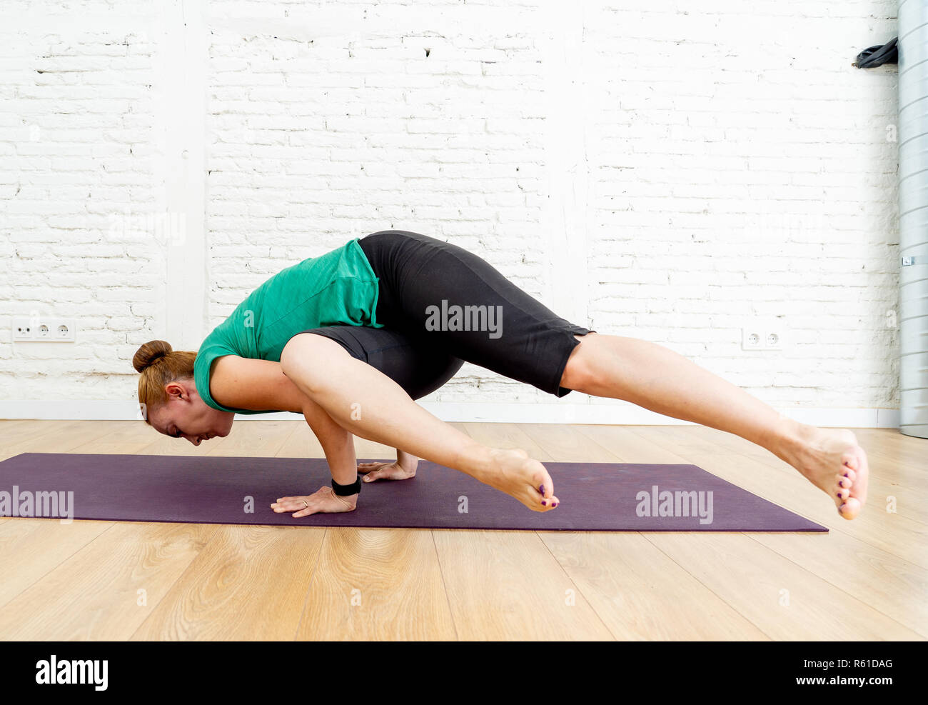 Attractive yogi woman teacher practicing advanced yoga in Parsva Bakasana exercise Side Crane pose at cool urban studio in Fitness Yoga benefits and E Stock Photo