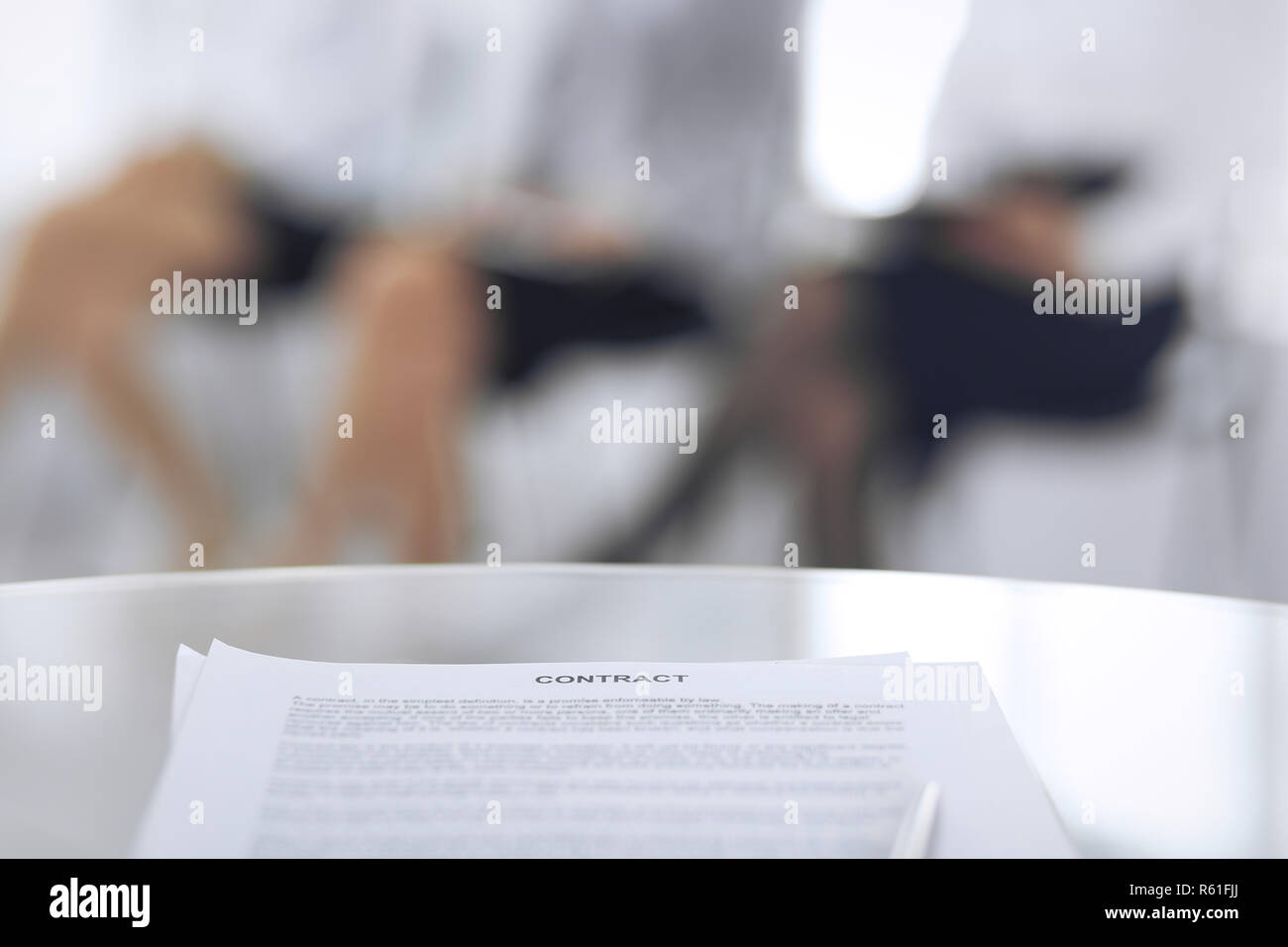 Contract with a pen and blurred business people on the background, close-up. Female candidates waiting for interview at queue - Stock Image