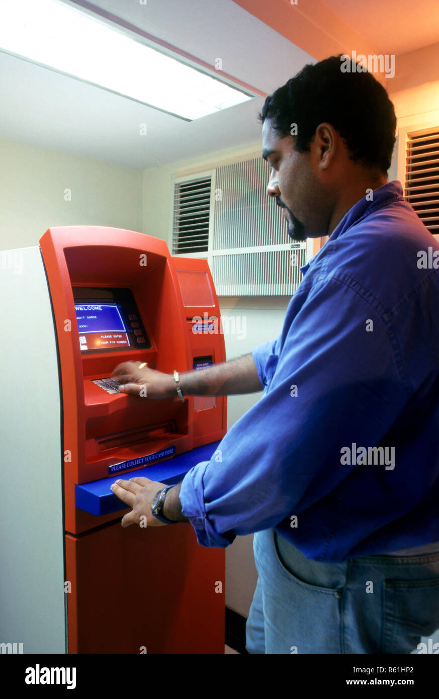 man operating Any Time Money System ATM, automated bank system - Stock Image