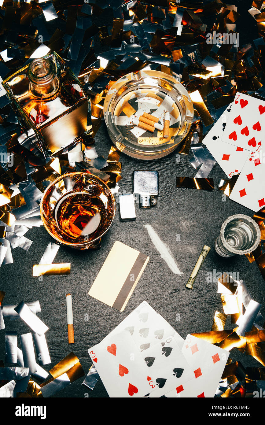 view from above of playing cards, cigarettes, whiskey, rolled banknote, credit card and cocaine on table covered by golden confetti Stock Photo