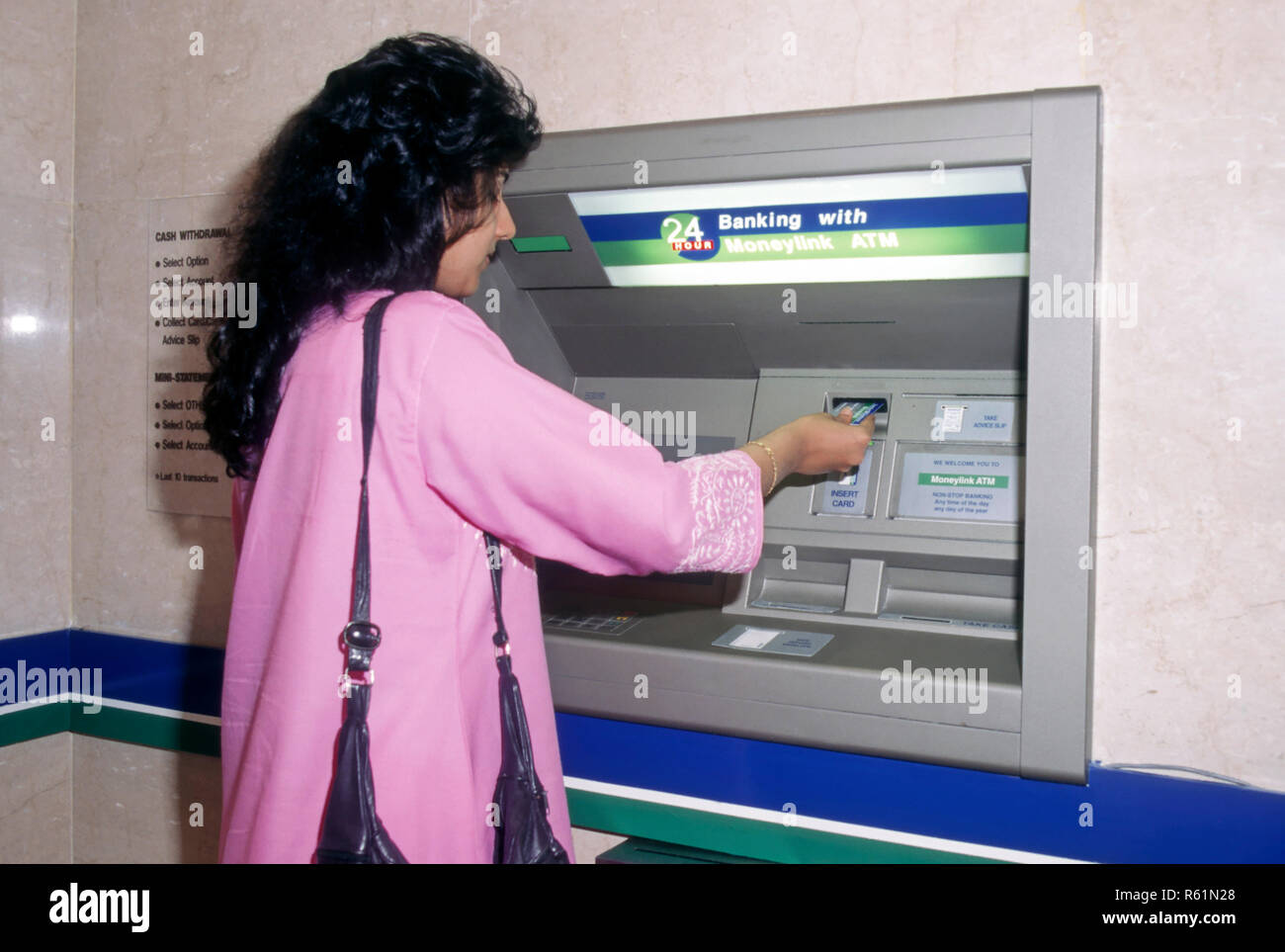 woman operating Any Time Money System ATM, automated bank system - Stock Image