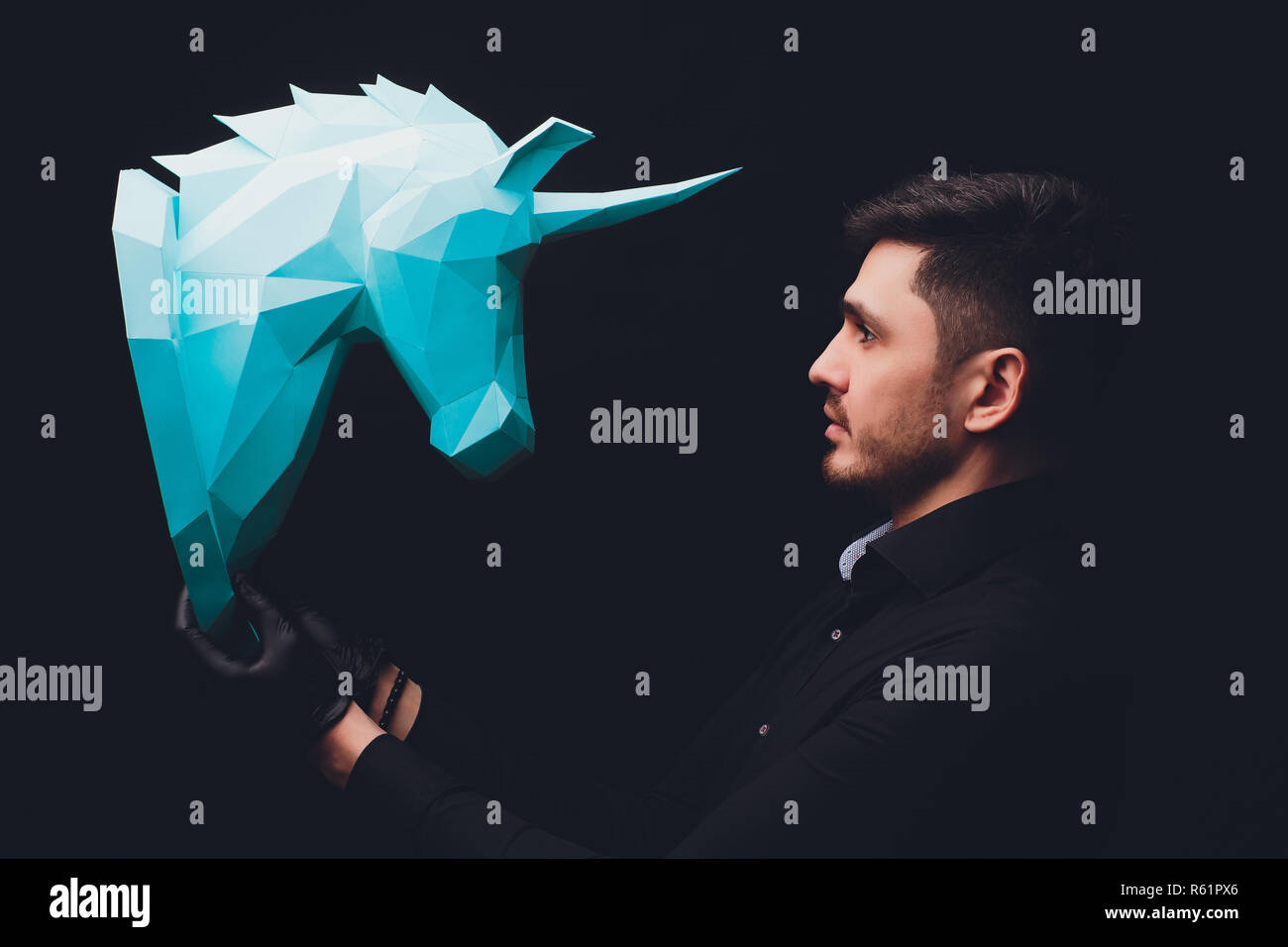 Man in black gloves holds origami. Unicorn turquoise head paper isolated on black background. Copy space. Model mythical creature. Male - Stock Image