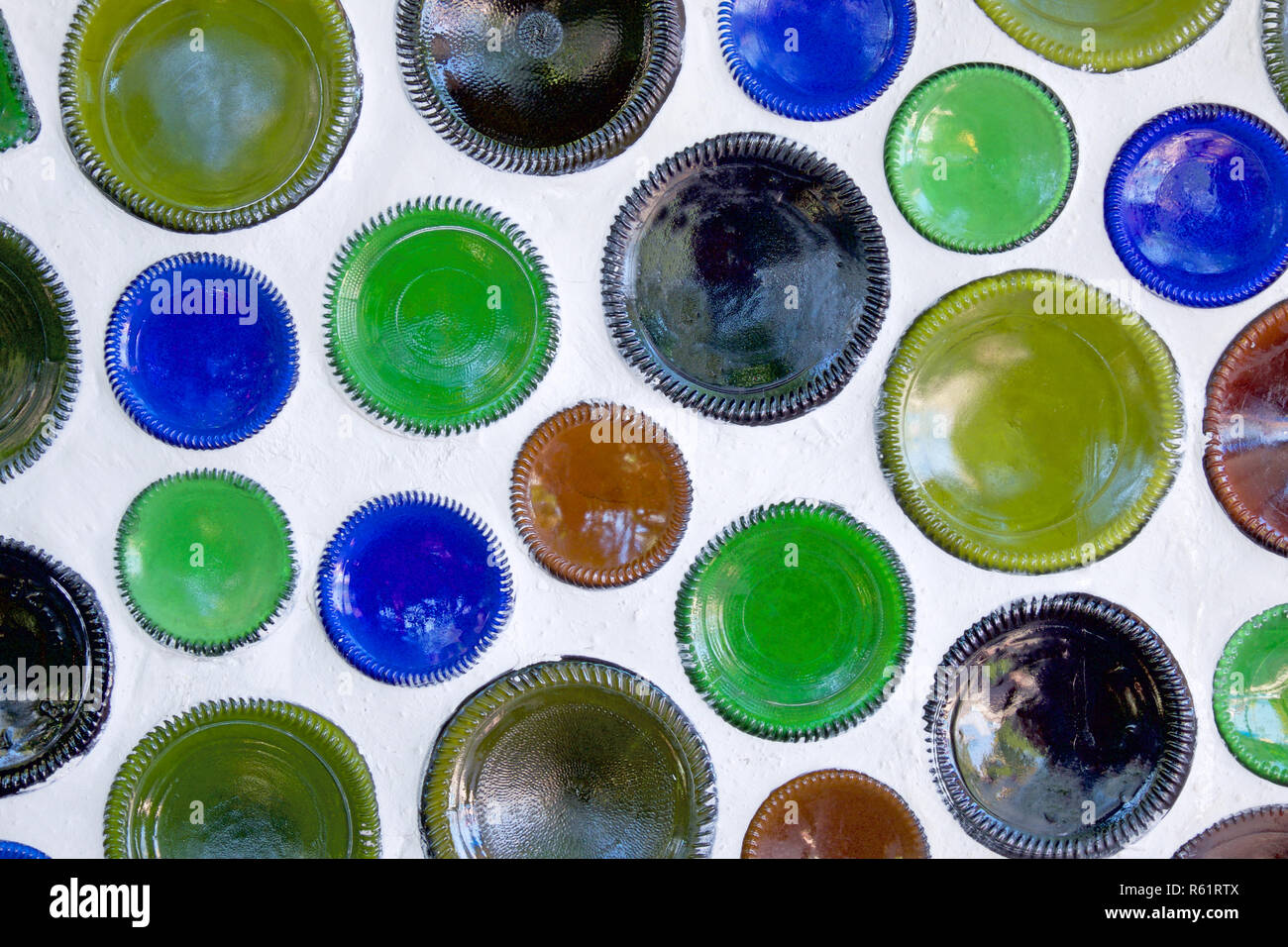Fifty circular glass bottles have been reused as building materials and the bottom of the bottles are built into a white wall, the bottles have just t - Stock Image