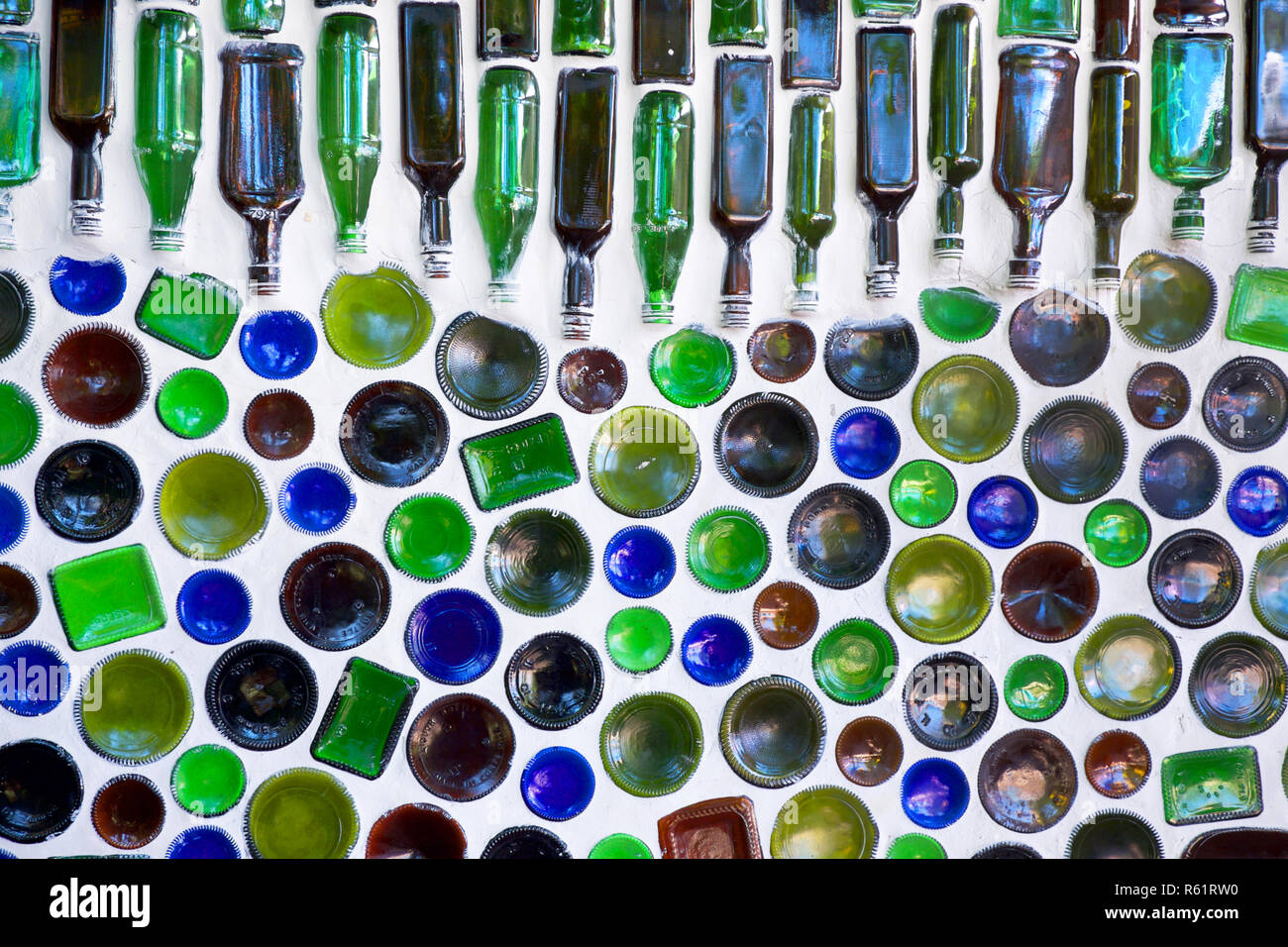 one hundred glass bottles built into a white wall, fifty of the bottles in the bottom of the image have just the bottom of the circular glass showing, - Stock Image