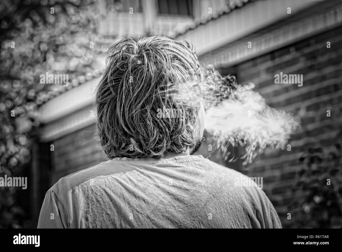 guy smokes vape and the company of young people on a walk in summer Stock Photo