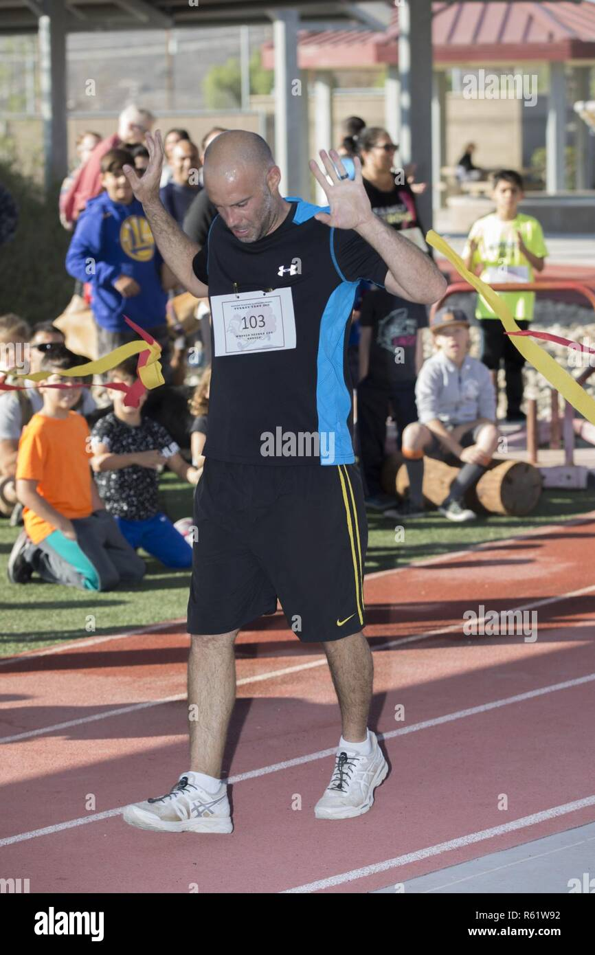 Michael Kleinert, a water sports specialist with Wounded Warrior Battalion West (WWBN-W), crosses the finish line during the 3rd annual Turkey Trot at the WWBN-W Headquarters, Marine Corps Base Camp Pendleton, California, November 21, 2018. The Turkey Trot was a fun run, competitive run and walk, and concluded with fun activities, prizes and food. - Stock Image