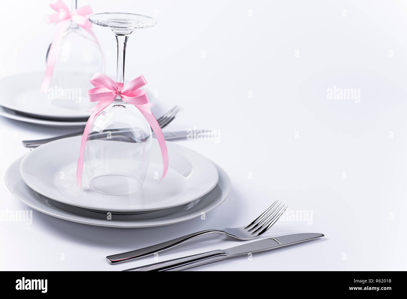Wine Glasses Turned Upside Down With Pink Decoration As Background