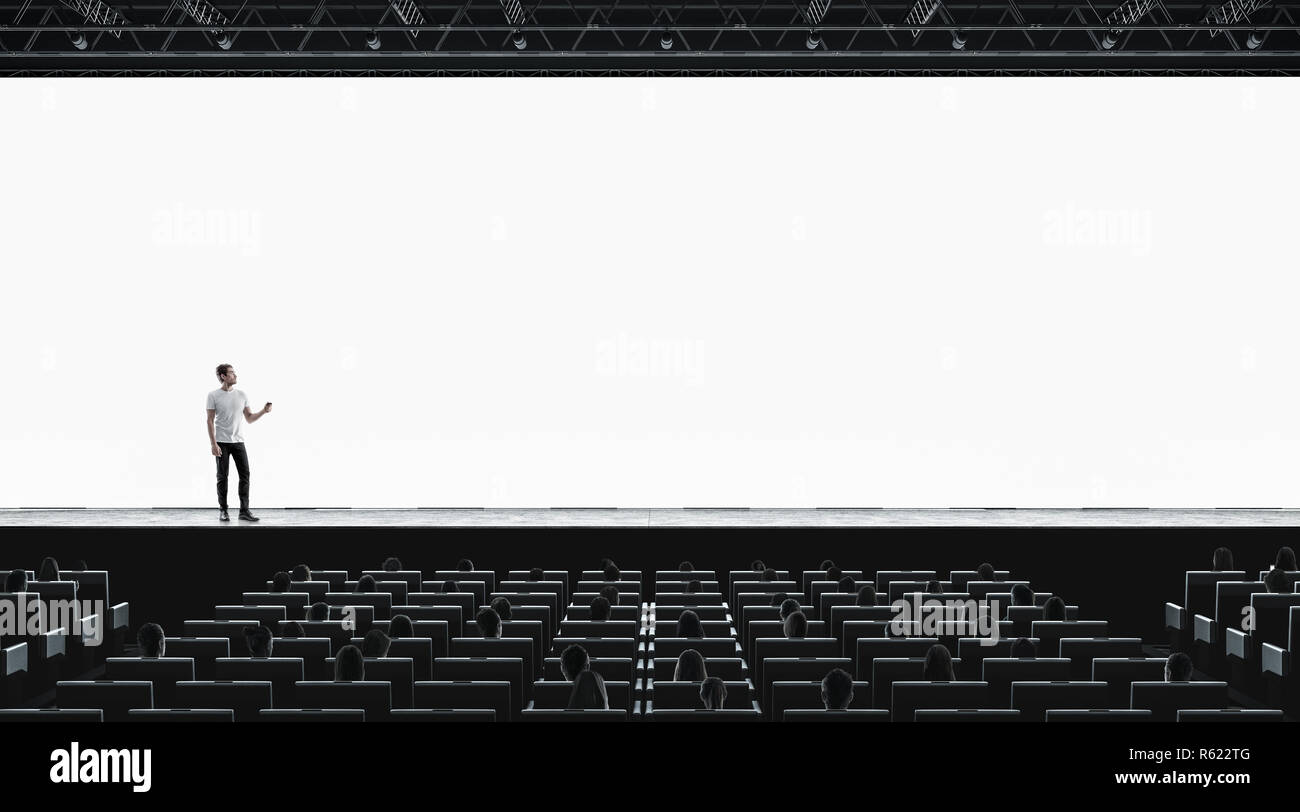 Presentation hall with person on scene auditorium watching on blank screen mockup. Empty display with speaker represent mock up. Public on training or forum template. - Stock Image