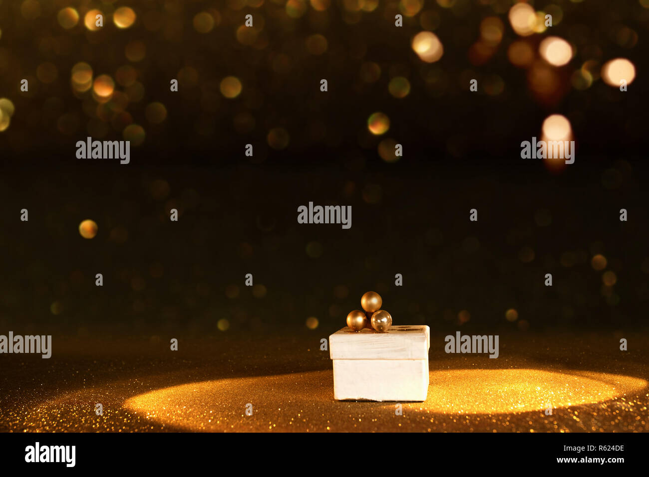 Golden bokeh background with a luxury gift in spotlight Stock Photo