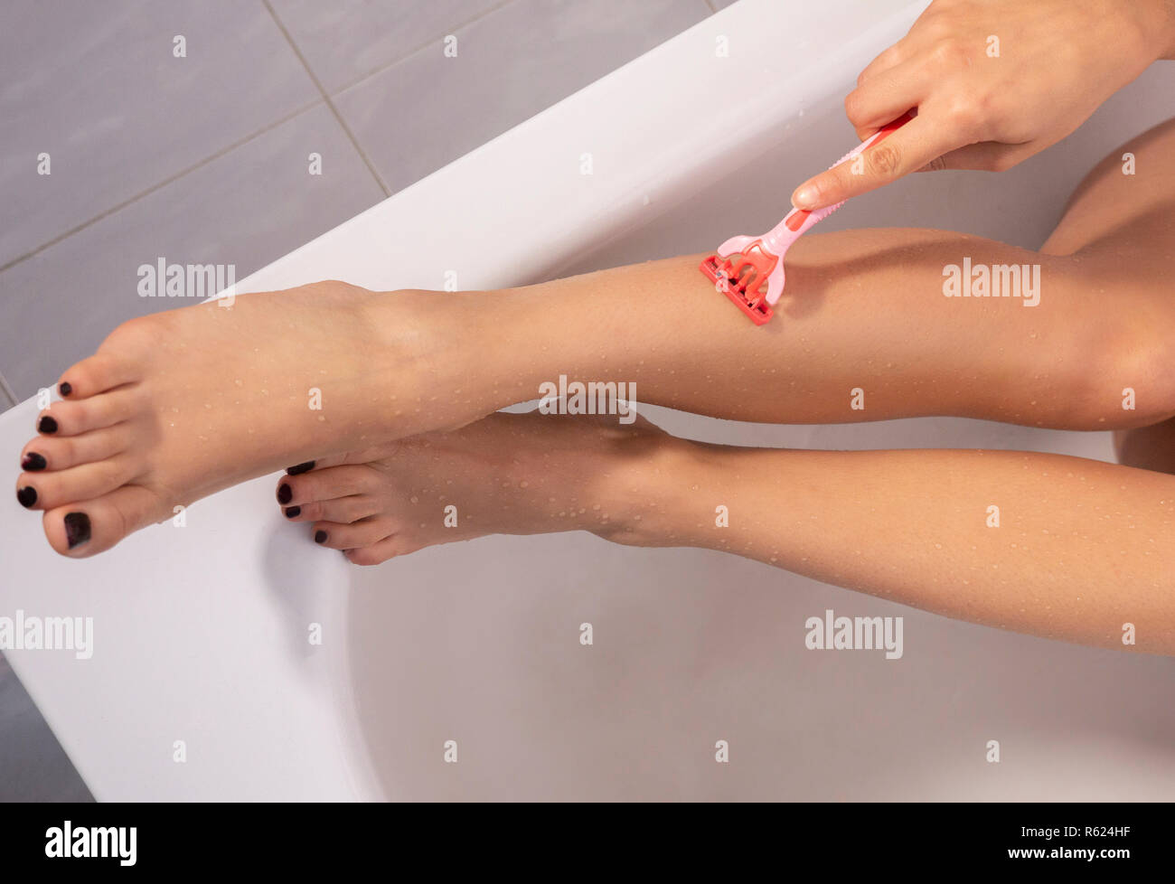 young woman shaving her legs with a razor blade - Stock Image