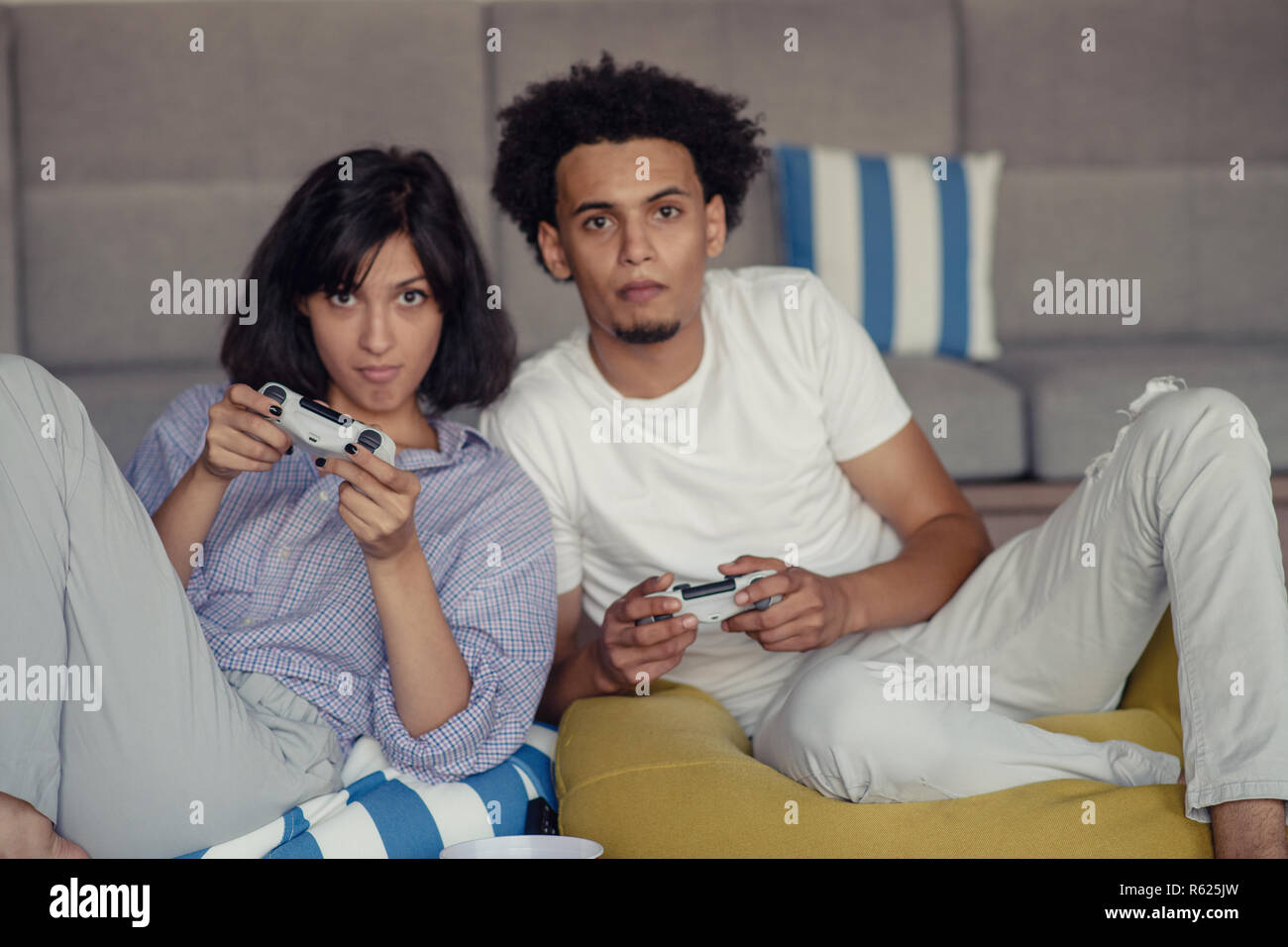 7f3cf0871e0c Playful young couple playing video games in their living room. - Stock Image