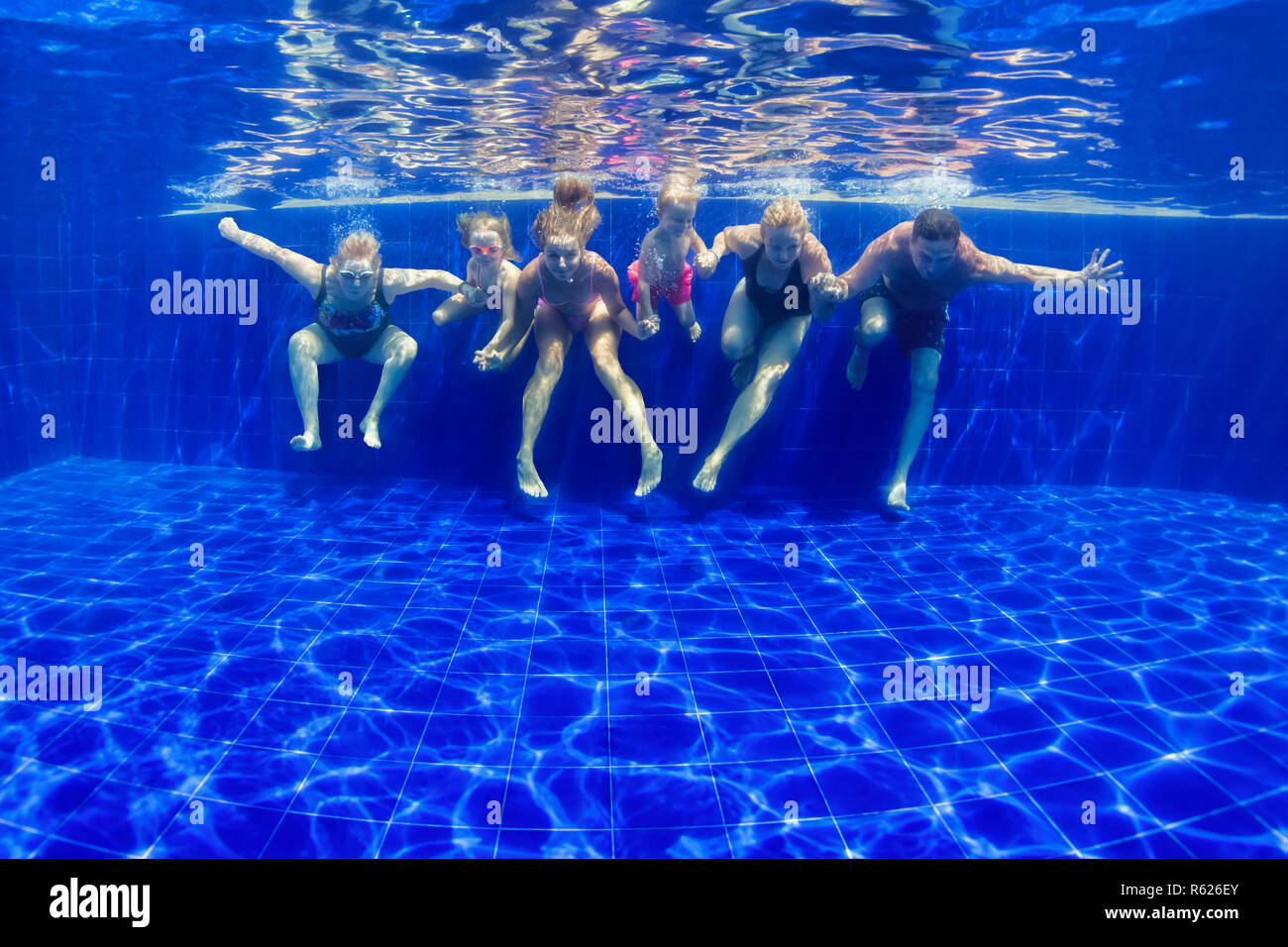 Happy family in swimming pool. Smiling mother, children and grandparents swim, dive in pool with fun - jump deep down underwater. Stock Photo