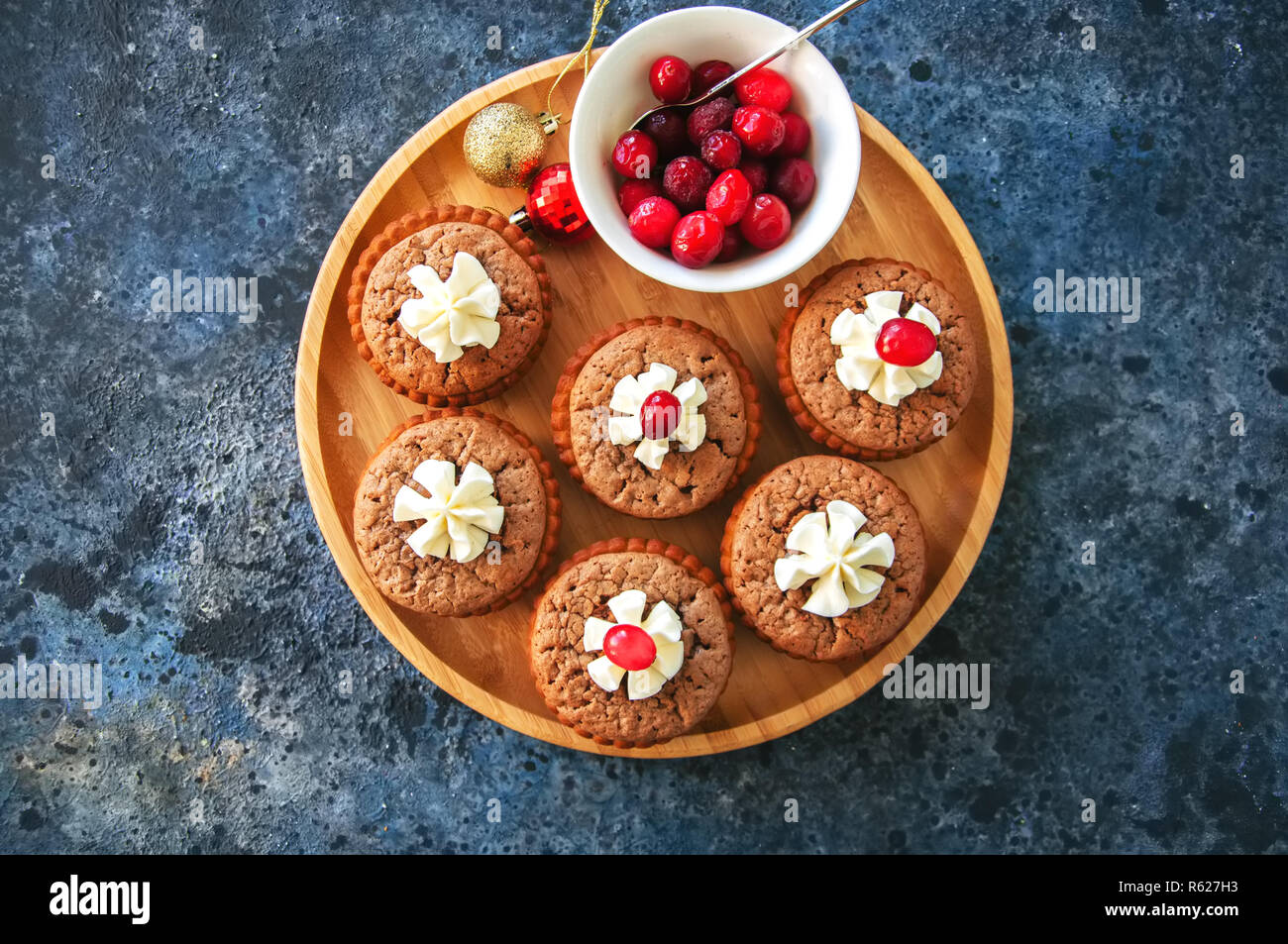 Brownie mins pies in a plate on a blue background. Festive desse - Stock Image