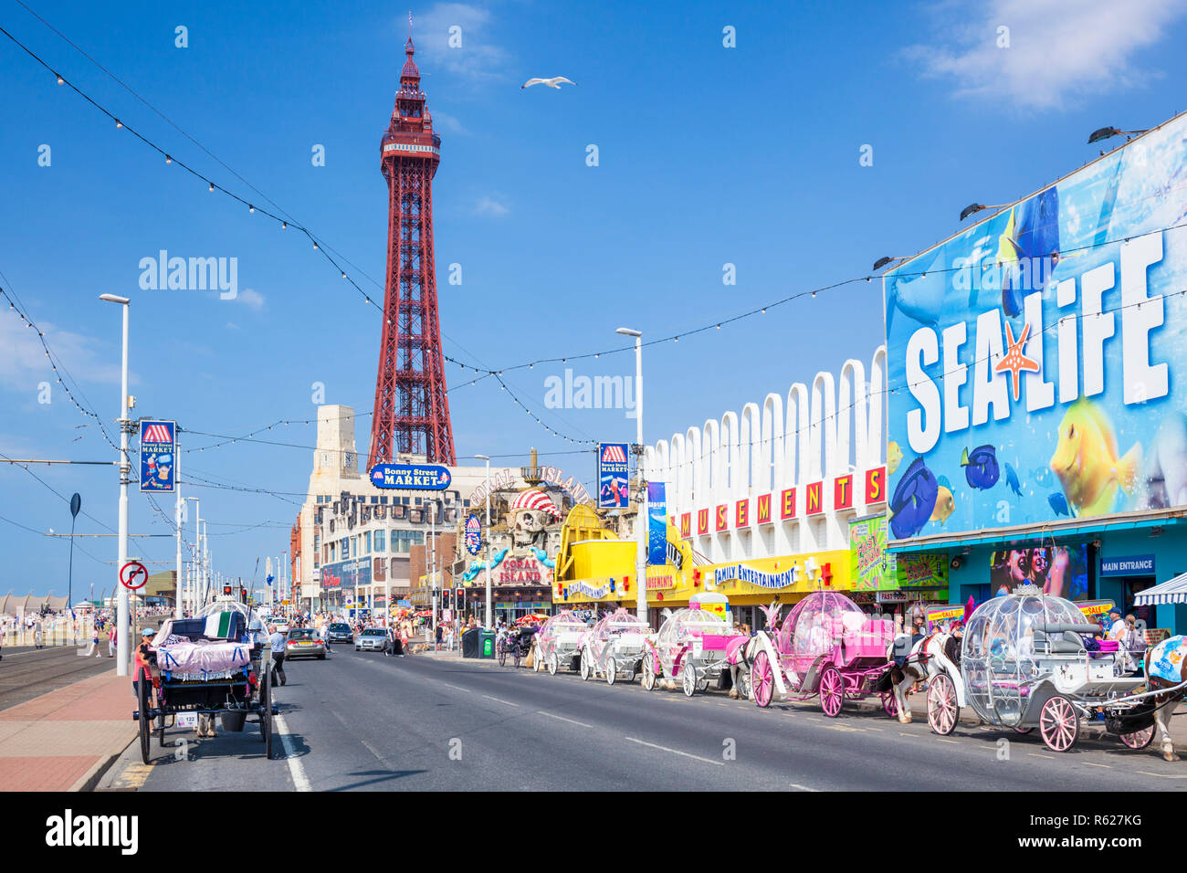 Blackpool tower and seafront promenade with Sealife centre aquarium amusements and horse drawn carriages Blackpool Lancashire England GB UK Europe - Stock Image