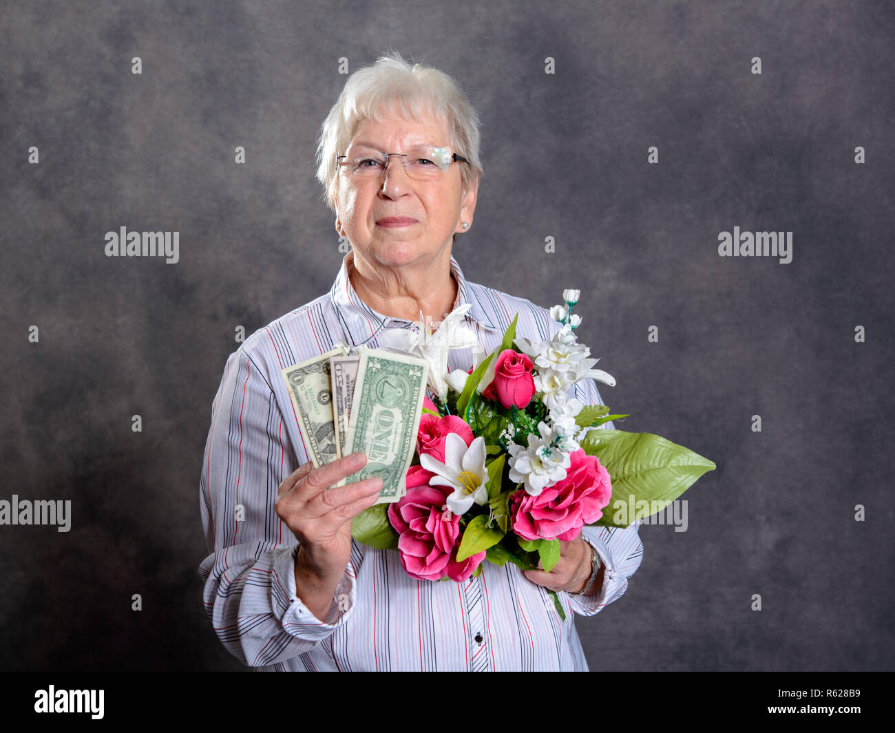 gray hairy woman with flowers and money - Stock Image