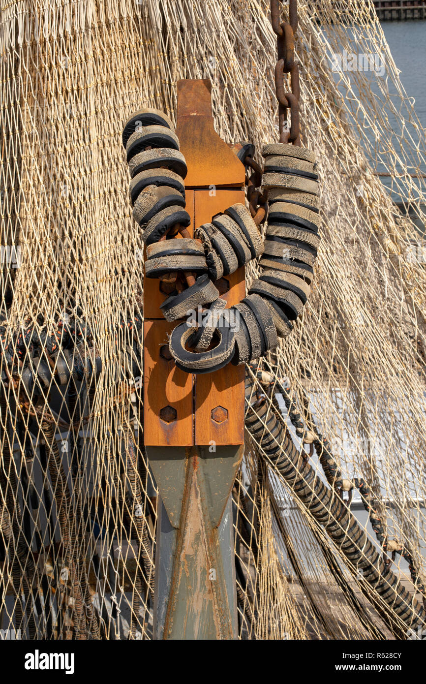 Fender on iron chain made of rubber at a fishing boat, at the background a fishing net. - Stock Image