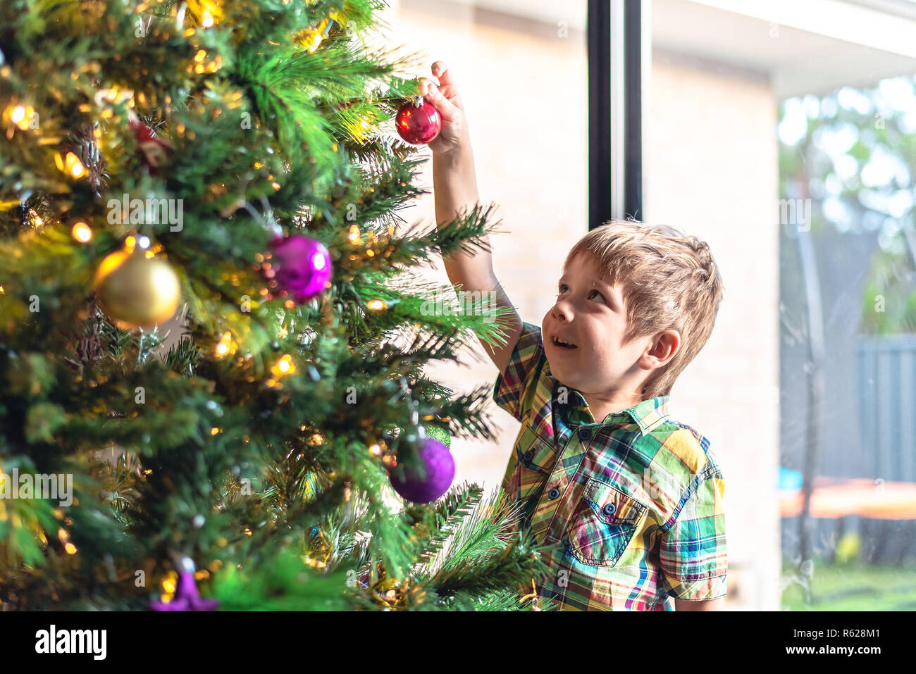 Cute smiling child decorating a Christmas tree in South Australia - Stock Image
