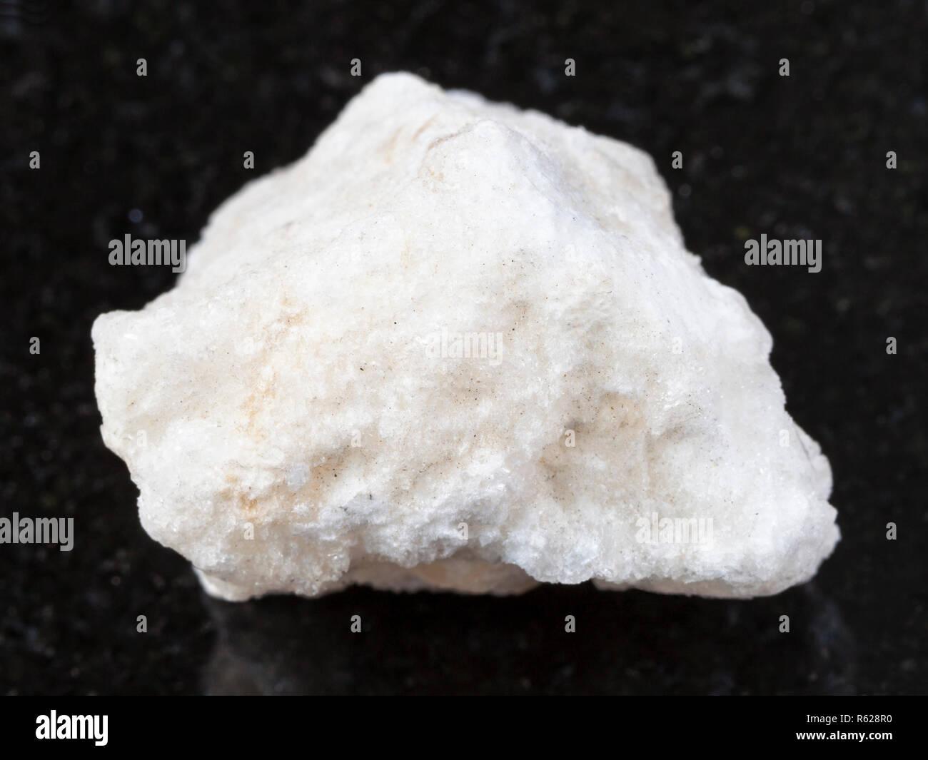 raw anhydrite stone on dark - Stock Image