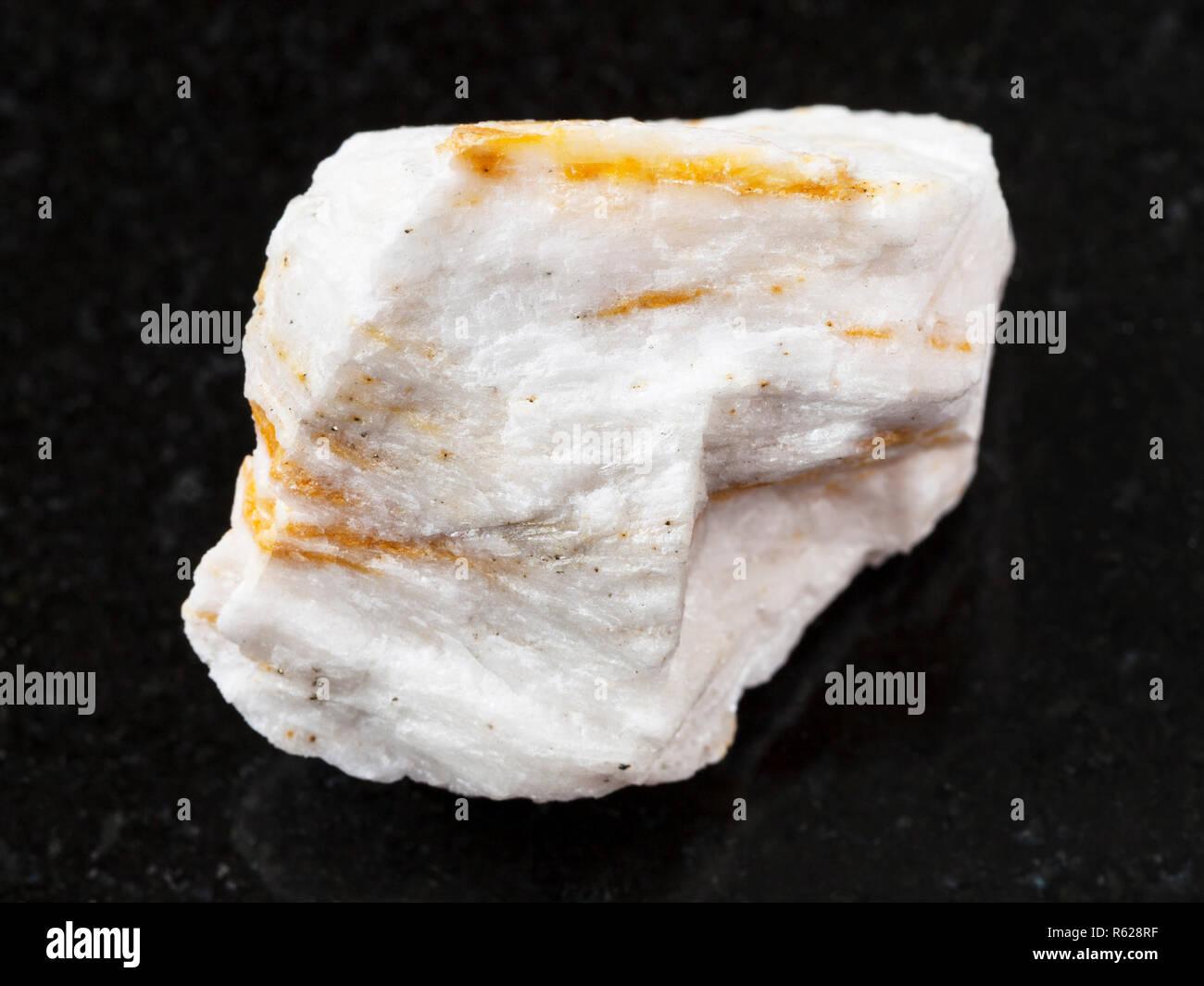 raw Baryte ore on dark background - Stock Image