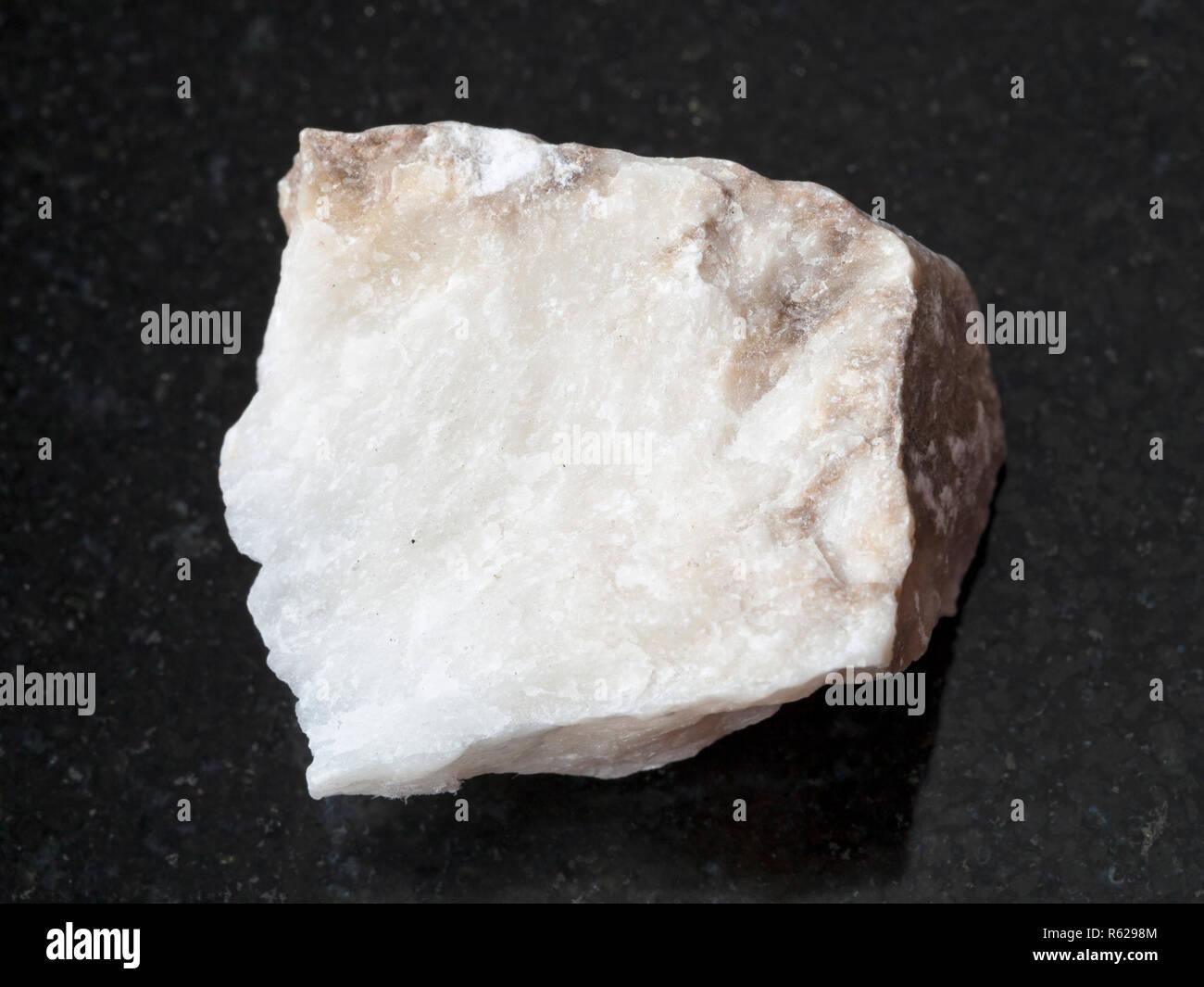 raw Anhydrite stone on dark background - Stock Image