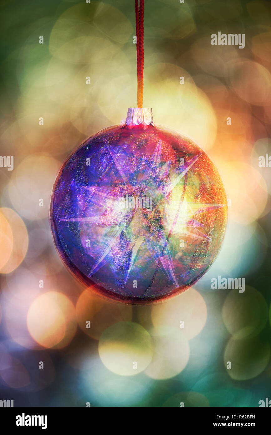 Artistic Christmas bauble hanging in front of out of focus lights (digitally enhanced) - Stock Image