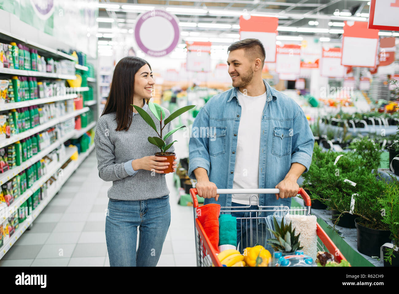 Couple With Cart Full Of Goods Buying Home Flower In A