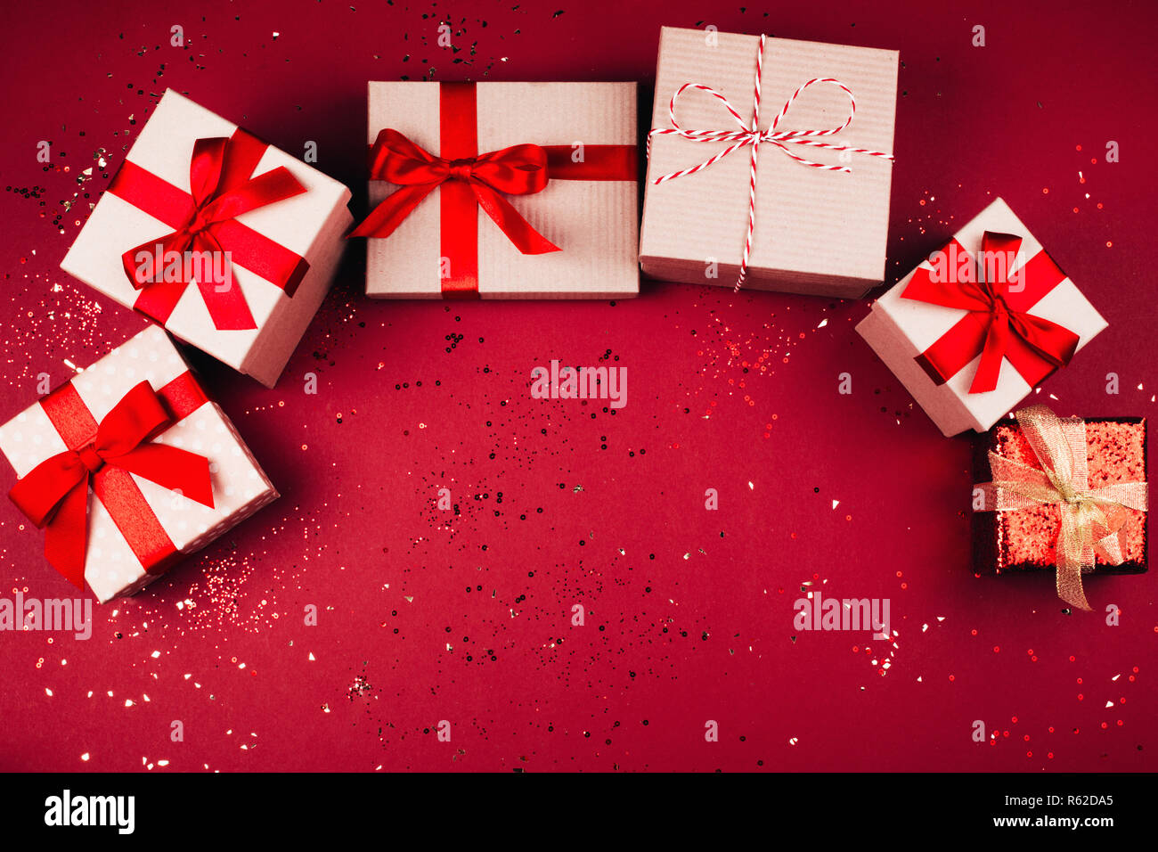 Many present boxes with red bow on red background. Flat lay style. Stock Photo