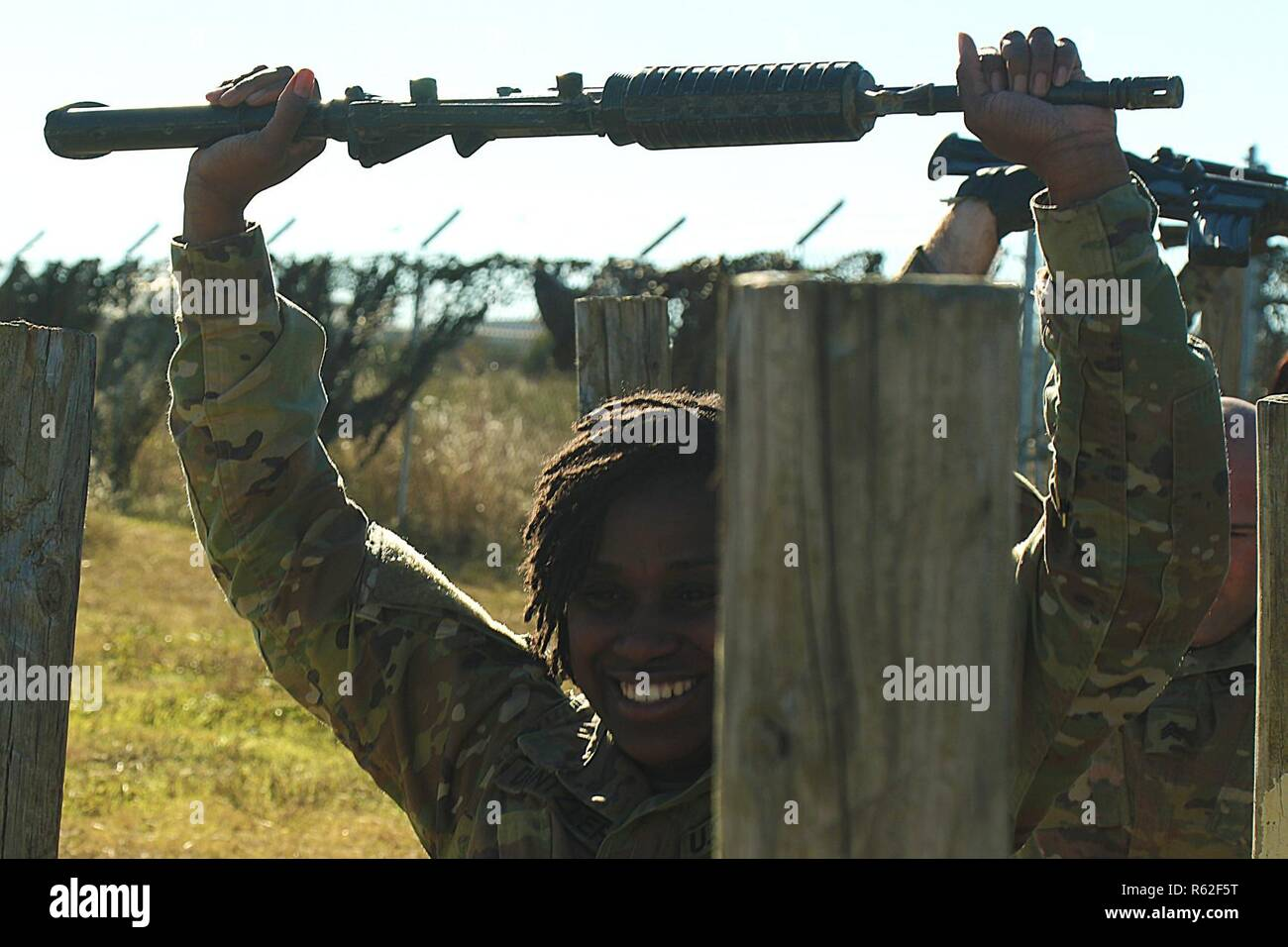Spc. Jasmine Dantzler raises her rifle over her head during the stress lane at the Phantom First Responder course November 16, 2018, at Fort Hood, Texas. The course, a combination of Tactical Combat Casualty Care - All Combatants (TCCC-AC) and Combat Lifesaver (CLS), teaches Soldiers how to respond under high levels of stress and provide care to casualties. - Stock Image