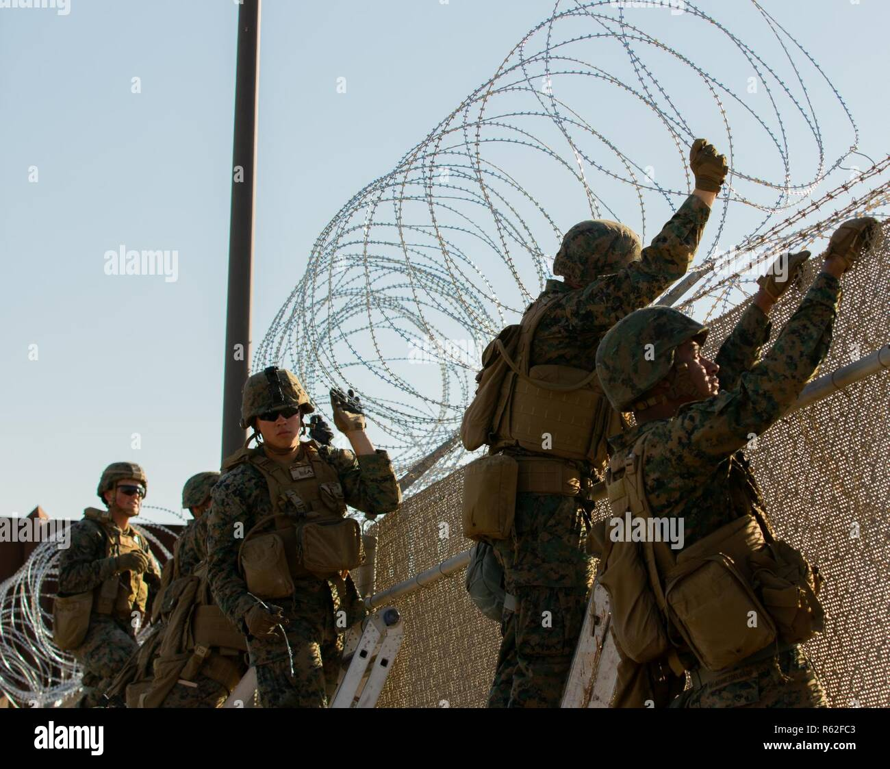 U.S. Marines from Special Purpose Marine Air-Ground Task Force 7 use concertina wire to strengthen the Calexico East Port of Entry in Calexico, California Nov. 18, 2018.  U.S. Northern Command is providing military support to the Department of Homeland Security and U.S. Customs and Border Protection to secure the Southern border of the United States. - Stock Image