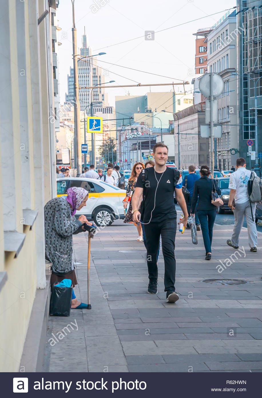 Moscow, Russia - September 6, 2018: Elderly woman asks for alms from passersby on the street. Retiree standing bent over with a cane cross oneself and asks for a money from people . Loneliness, poverty and social exclusion. People indifferently walk pass by old woman begging for bread - Stock Image
