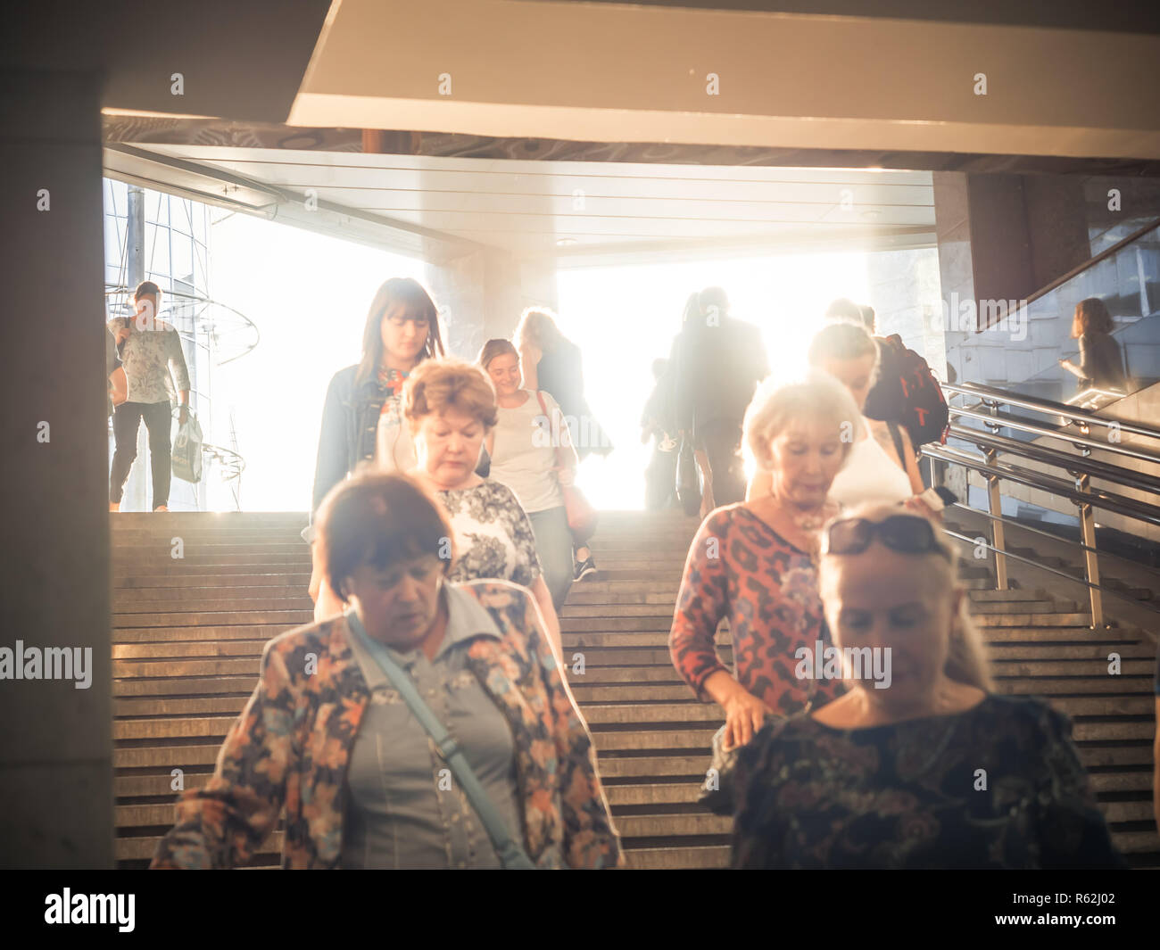 Moscow, Russia - September 6, 2018: Ordinary people go up and go down to the underground subway at rush hour. People go down to the underpass. Silhouettes of people walking down the steps against the backdrop of the sun. - Stock Image