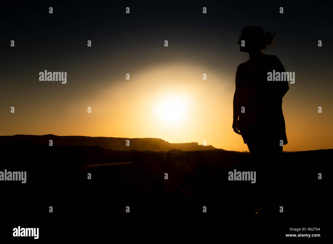 Silhouette of young girl with sunset in Namibe Desert. Africa. Angola. - Stock Image