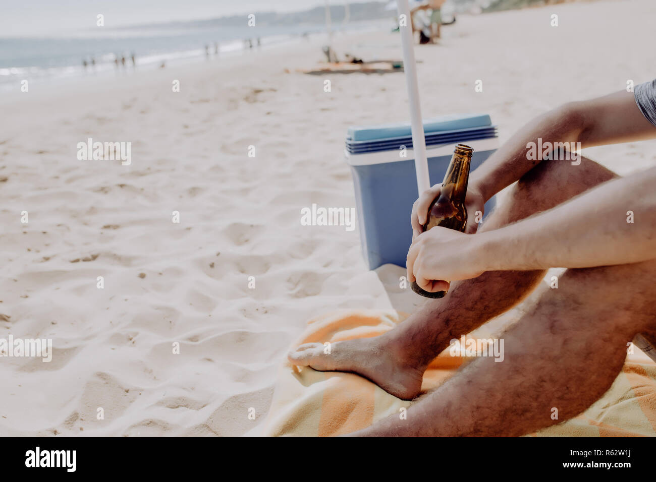 Cropped photo from back of man casual summer outfit drink beer bottle for cooler during party at seaside - Stock Image