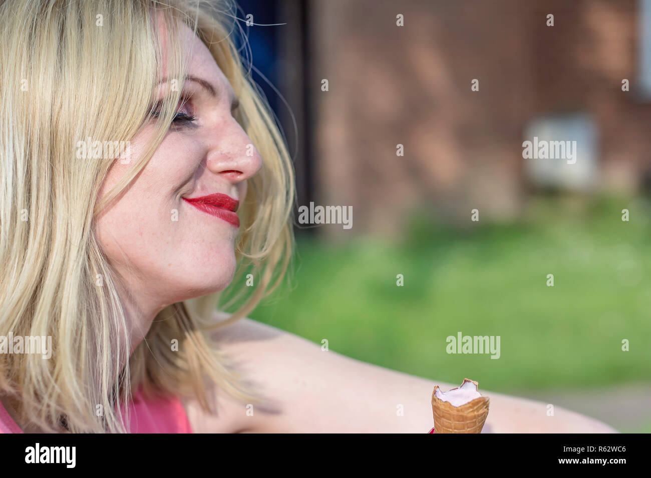 Young woman eating an Ice cream on warm summer day.Portrait of happy person on british council estate.Natural woman concept.Space for copy. - Stock Image