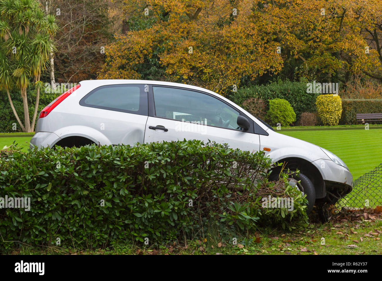 Poole, Dorset, UK. 3rd Dec, 2018. A bad bit of parking at Poole! Ford Fiesta Finesse silver car ends up on by hedge damaging fence. Credit: Carolyn Jenkins/Alamy Live News - Stock Image