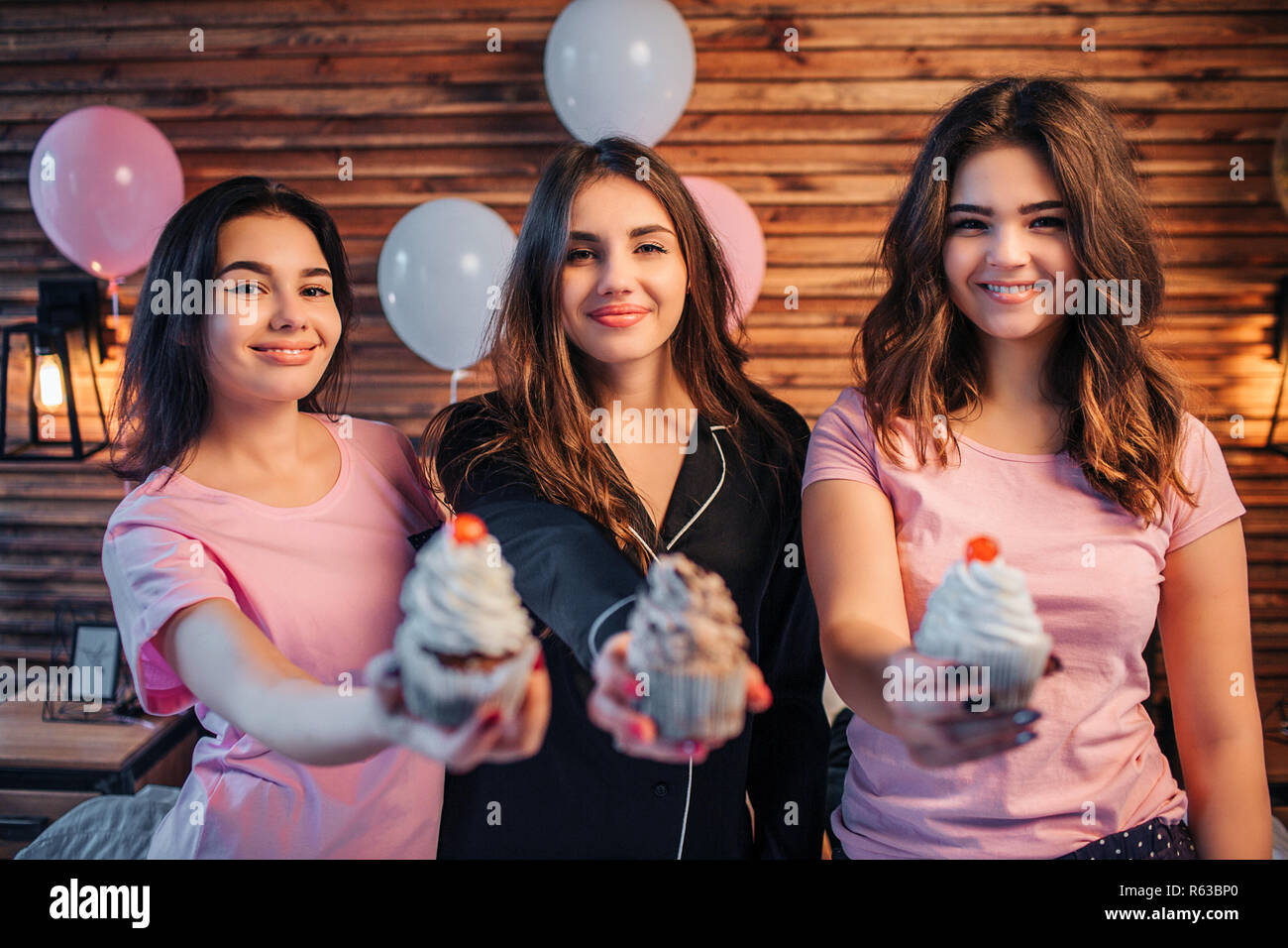 Three Young Women Stand And Look On Camera They Dmile People Hold Cakes In Hands Show It Looks Tasty Have Par