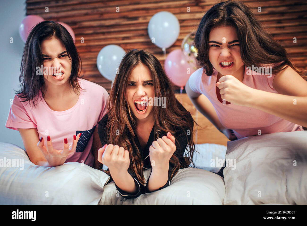 Emotional young women look on camera. They sit on bed with angry faces. Girls are very emotional Stock Photo