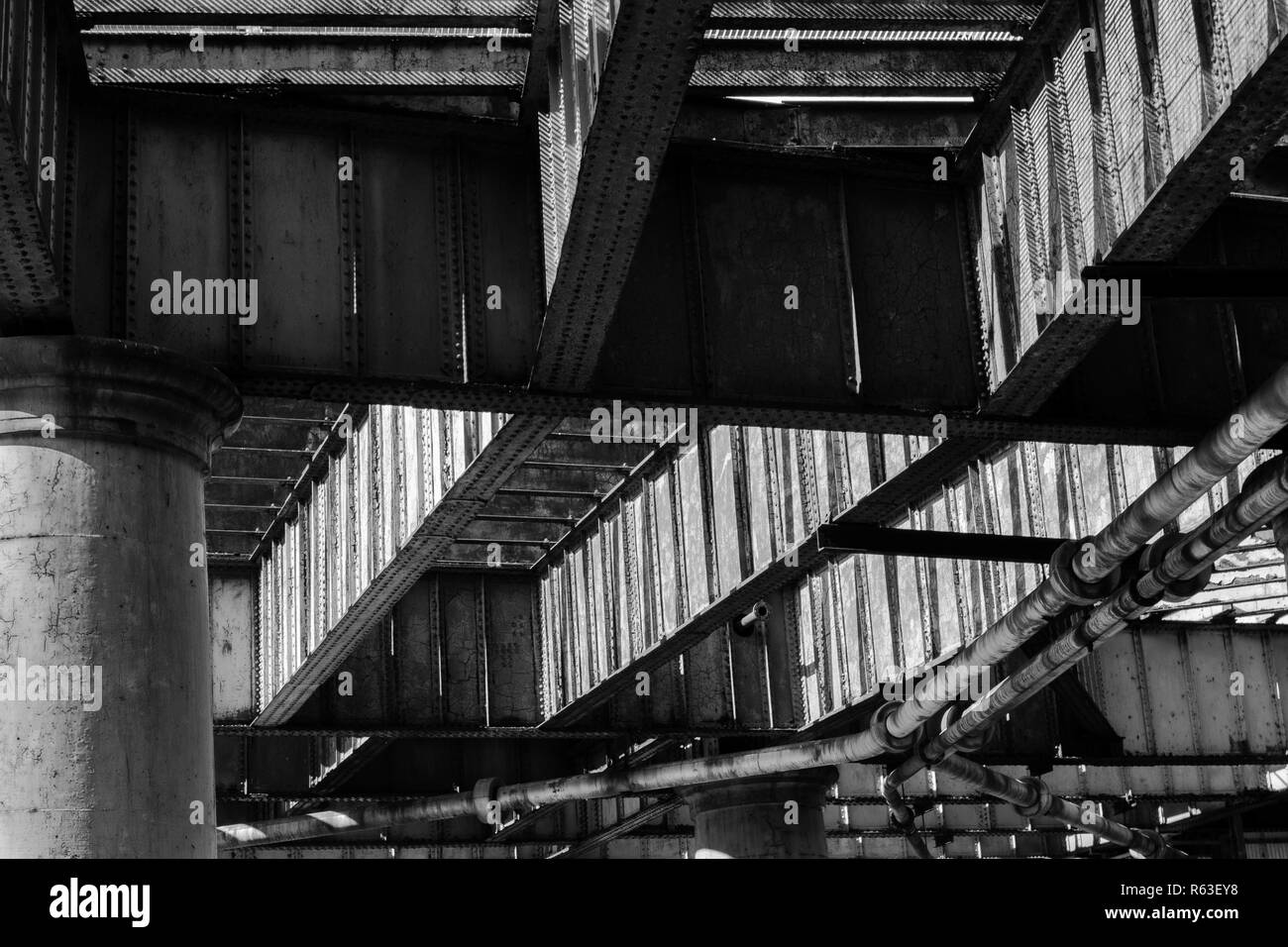 Metal beams and concrete columns of river pier underside - Stock Image
